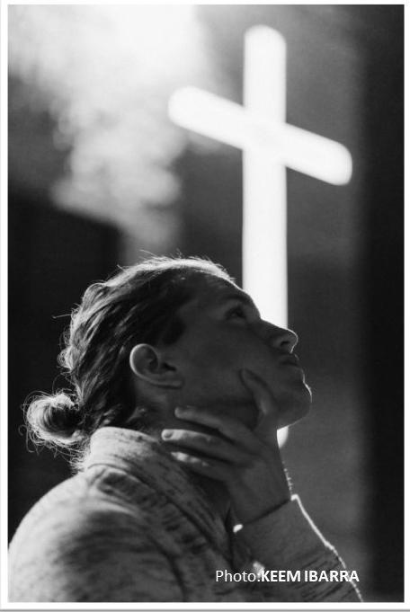 Praying girl at cross